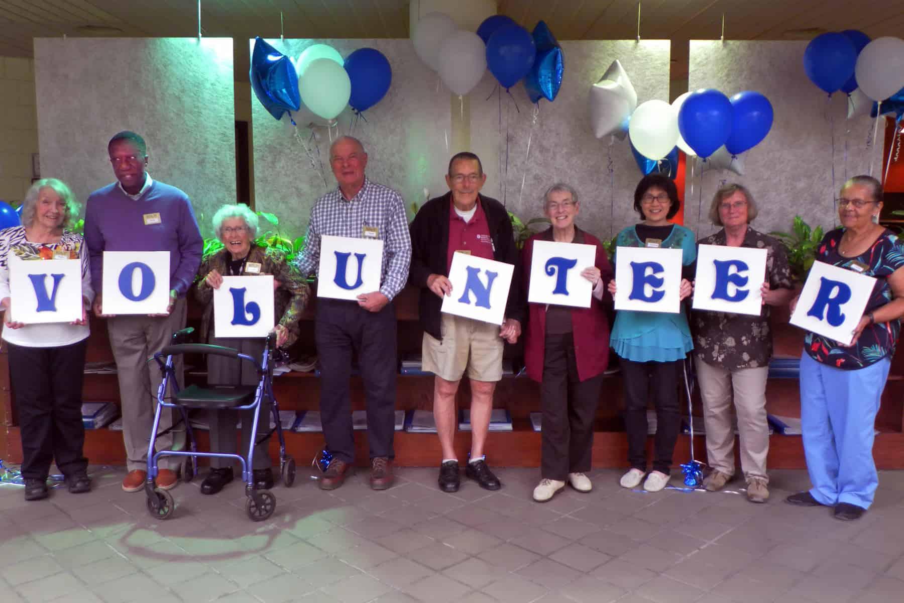 """RSVP Volunteers holding letters reading, """"Volunteer"""""""