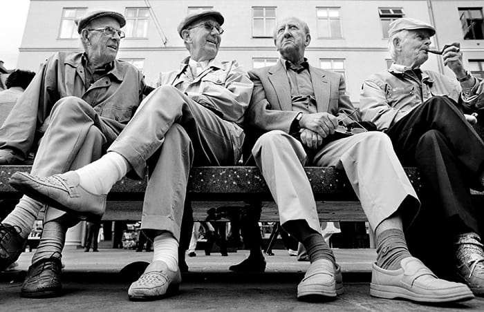 4 happy, older men sitting on a city park bench.