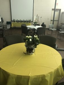 Round dining table covered with gold tablecloth and flower centerpiece.