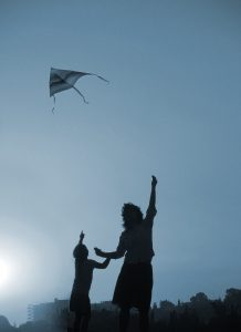 Silhouette of woman and child flying a kite