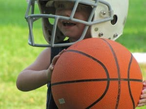 Boy wearing football helmet and carrying a basketball