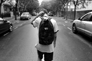 Distraught teenage boy with backpack in the middle of a street